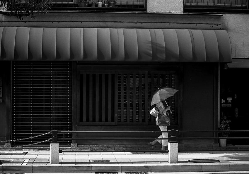 Umbrella walking in front of shop