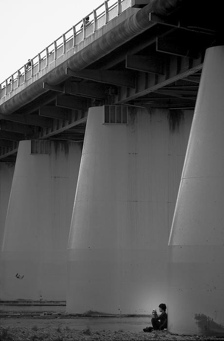 Young man at bridge pier