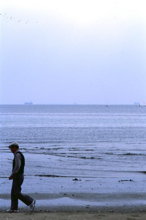 Old man walking beach