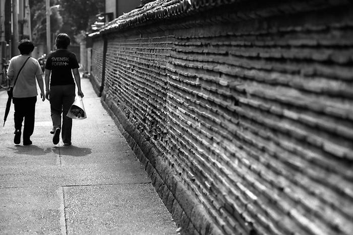 壁沿いを歩く人