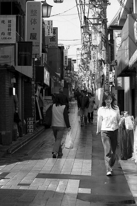 クリーニングを手に歩く女性