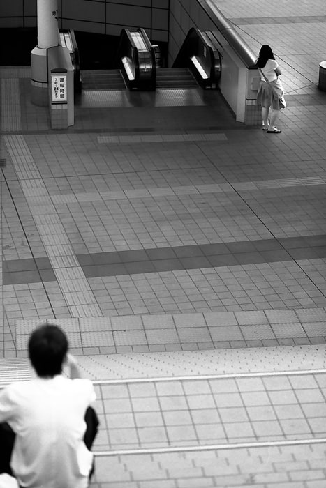 boy on stairway and woman beside escalator