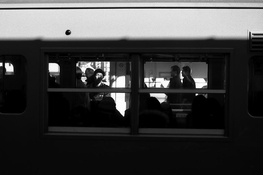 電車の窓の向こうに見える男