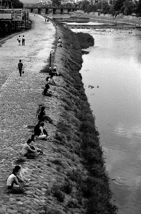 鴨川沿いに腰掛けるカップル