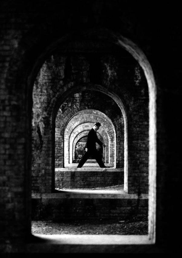 Man walking between bridge columns
