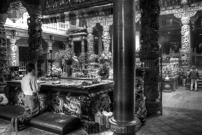 寺院で跪いく男