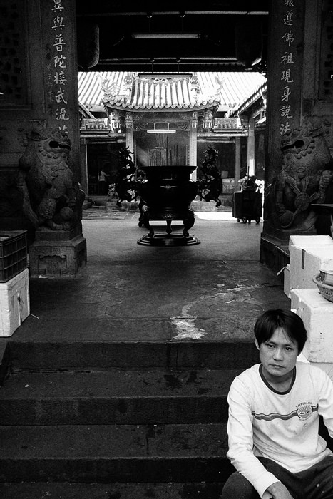 Man sitting at entrance of temple