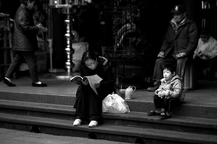 Young Woman Reading A Brochure And An Anxious Boy (Taiwan)