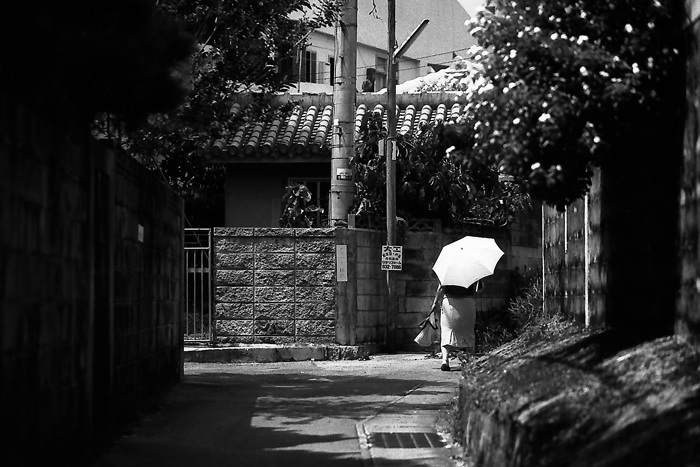 Older Woman With An Umbrella And A Bag (Okinawa)