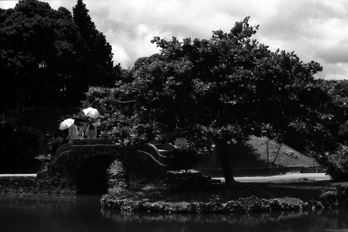 Three umbrellas on stone bridge