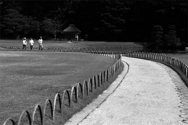 Three Persons Walking The Winding Path In Korakuen (Okayama)