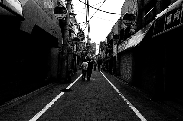 Couple Walking Between White Lines (Tokyo)