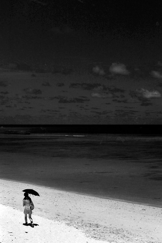 Woman walking beach with black sunshade