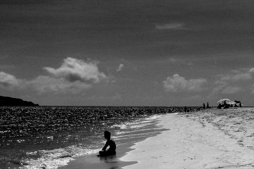 波打ち際に腰掛けた若者のシルエット