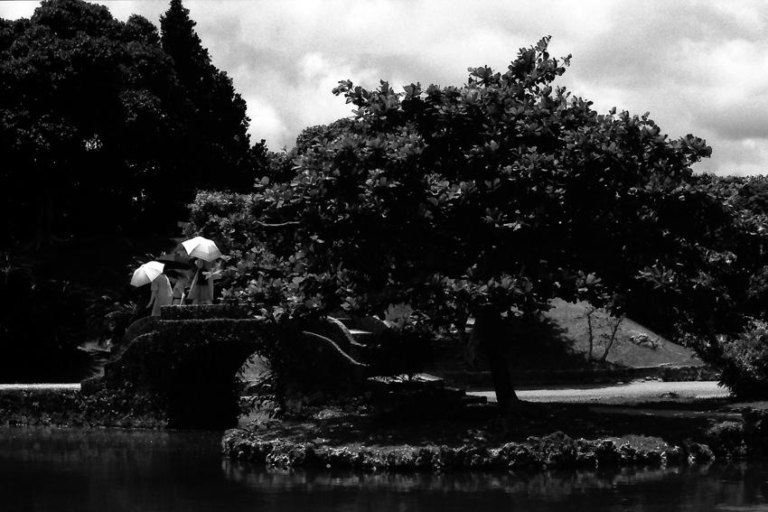 識名園の石橋の上を歩く傘