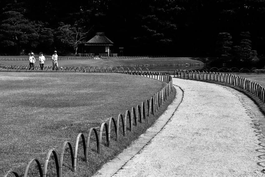 Three persons walking path in Korakuen garden