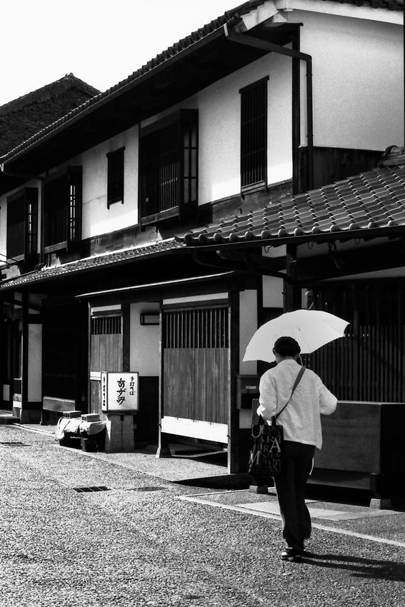 傘を差して歩く女
