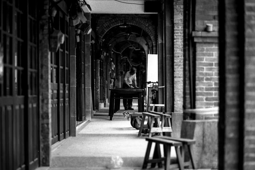 Man working in passage in Minchuan Old Street