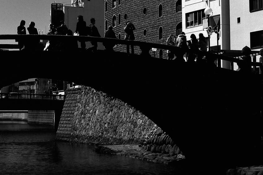 silhouettes on black bridge
