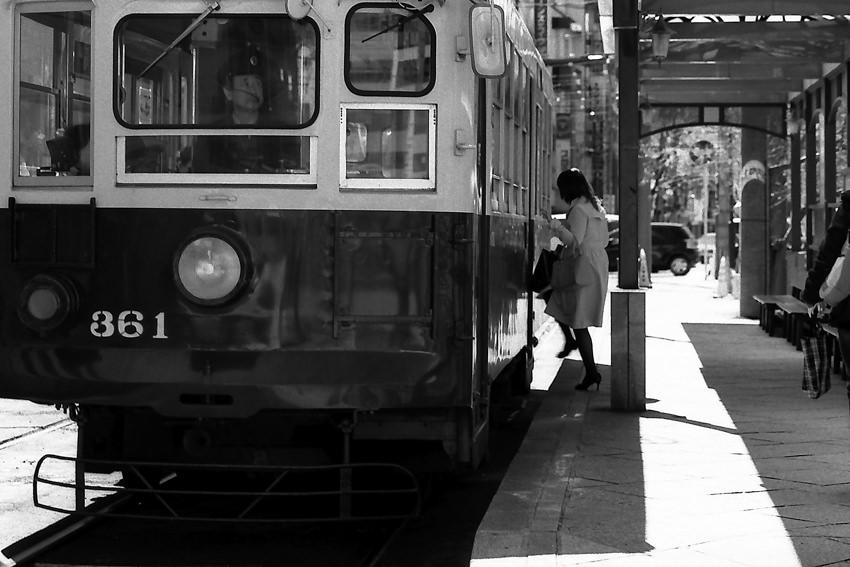Woman getting on tram