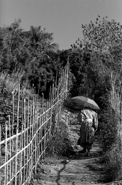 日傘を差して坂道を登っていく僧侶