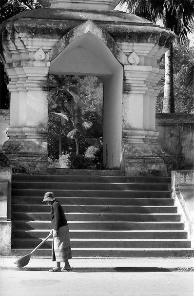 Woman sweeping in front of Buddhist temple