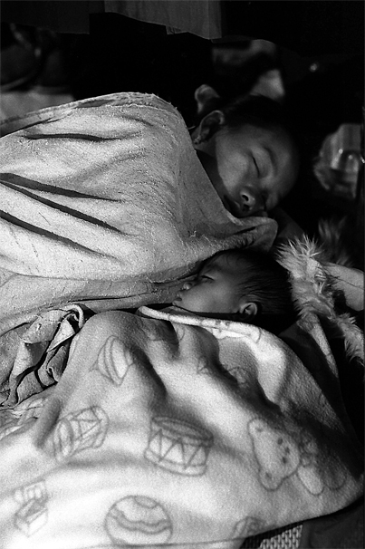 Mother And Her Baby Sleeping In The Night Market (Laos)