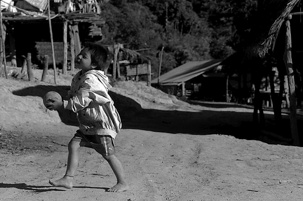 Shoeless Boy Playing With A Ball (Laos)
