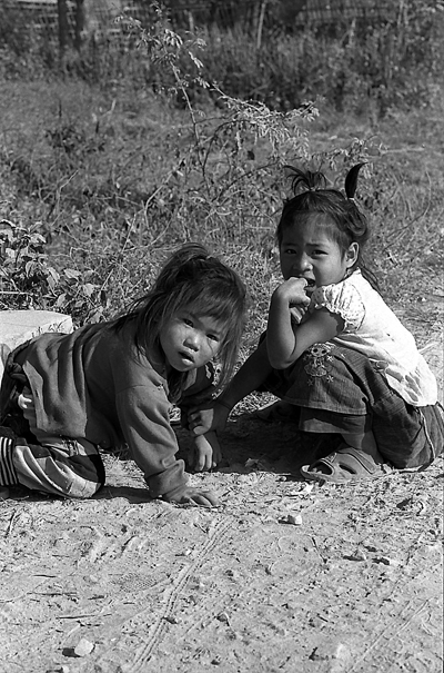 Two Girls Sitting On The Dirt Road (Laos)