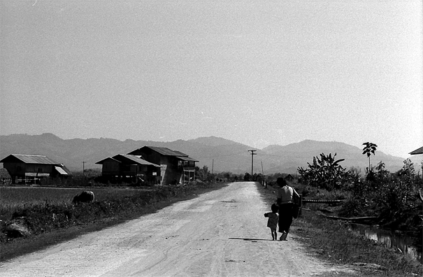 Mother And Her Son Walking The Straight Road (Laos)