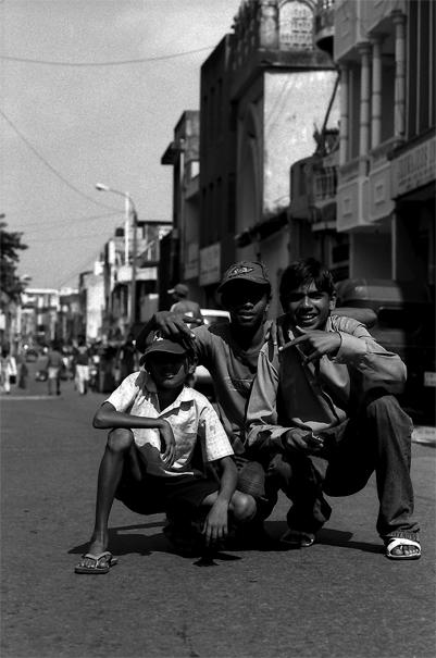 Three Boys Squatting Down In The Street (Sri Lanka)