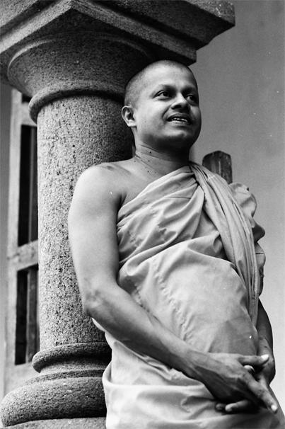 Monk Leaning Against A Pillar (Sri Lanka)