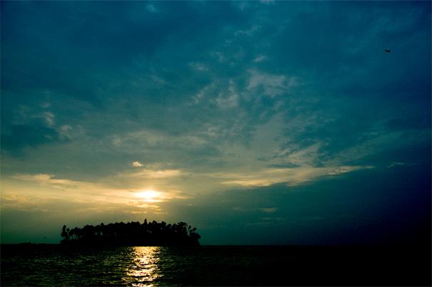 沖合の島の向こうに沈んでいく太陽