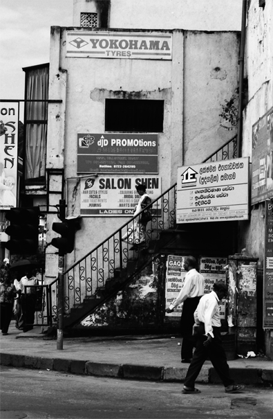 Woman with a saree descending stairway in front of advertisement