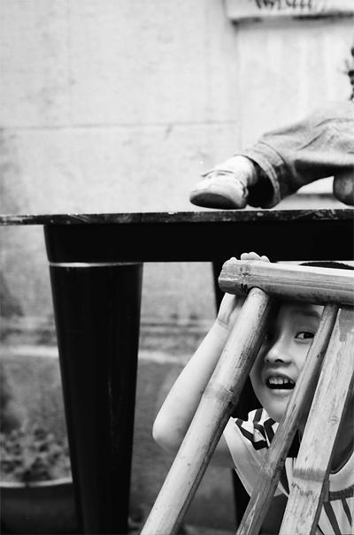 椅子の陰から見る男の子
