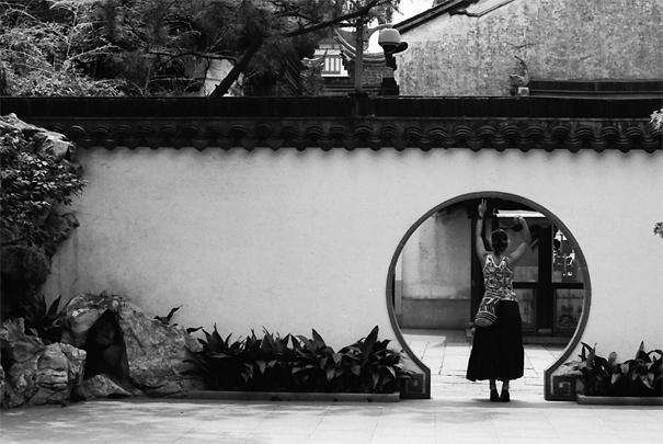 塀にある穴のところに立つ女性