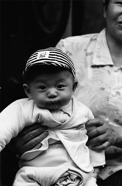 ストライプの帽子を被った落ち着いた赤ん坊 (中国)