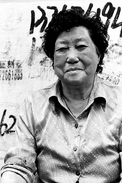 路地の片隅で笑う女性