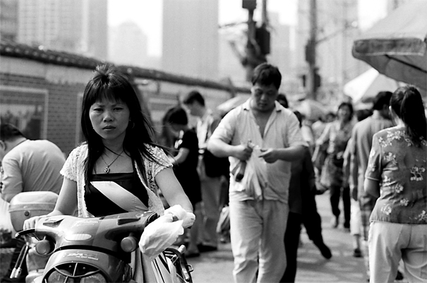 露天市の中でバイクに跨る女性