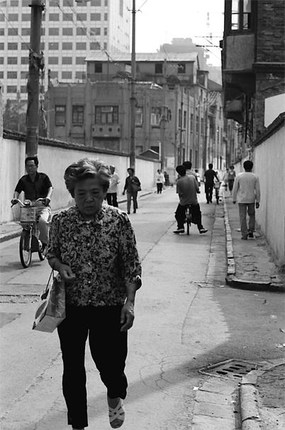 うつむきながら歩く年配の女性