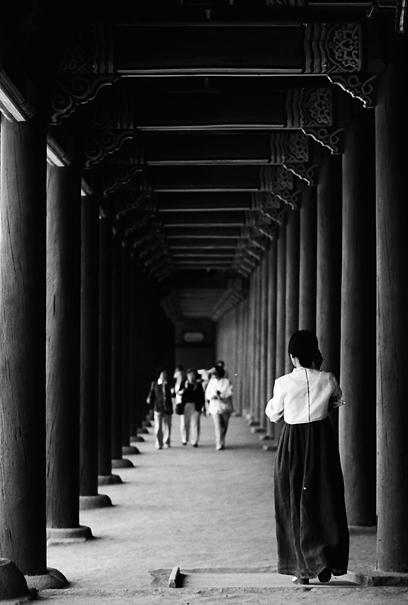 回廊を歩くチマチョゴリを着た女性