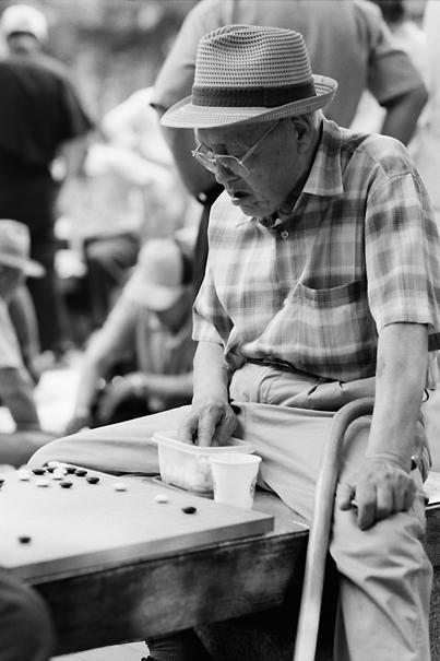 公園で碁を指す老人