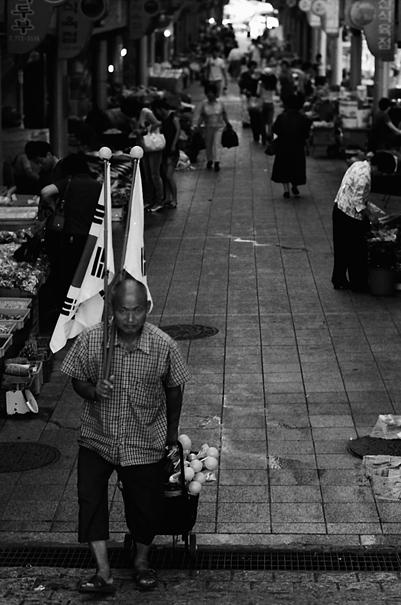 韓国の国旗を抱えて売り歩いていた男