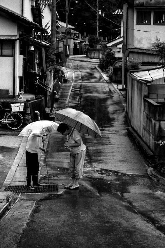 Two women standing in rain