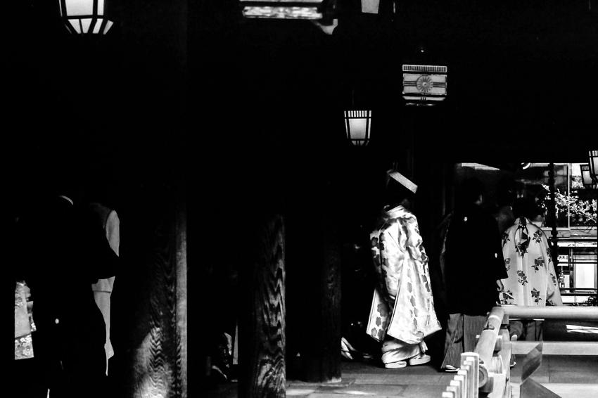 Bride walking the dark cloister in Meiji Jingu