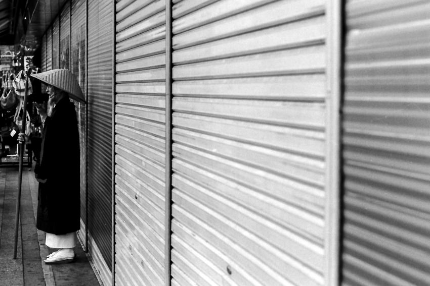 Buddhist monk standing in front of shutter
