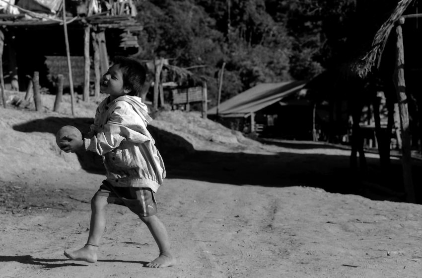 Shoeless boy playing with ball