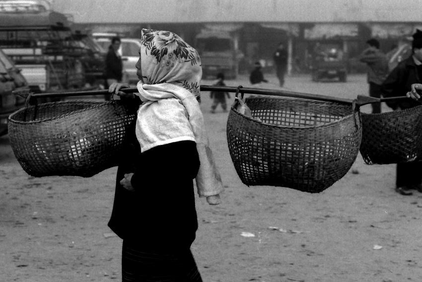 Woman carrying yoke in market