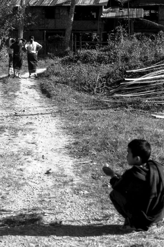 Boy crouching at entrance of path