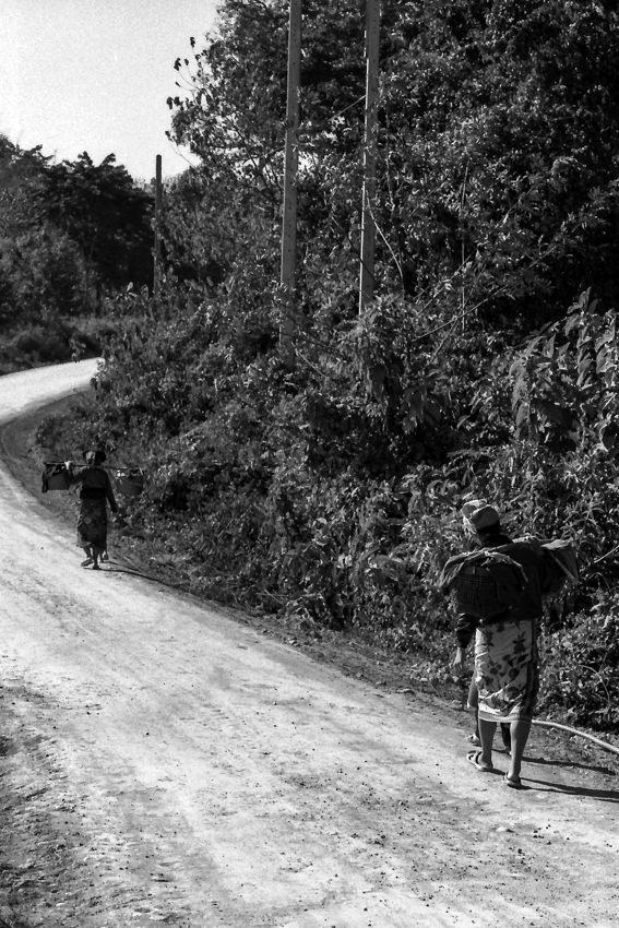 Women walking dirt road with burden